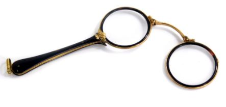 An early 20thC tortoiseshell and gold coloured metal lorgnette, each with a tapering handle cast wit
