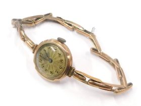 A 9ct gold cased ladies wristwatch, the small circular gold coloured dial with blue hands in a 9ct g