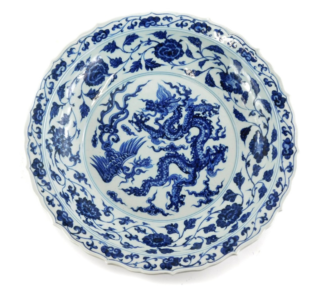 A Chinese blue and white charger, with a shaped edge decorated in blue with dragon, six character ma