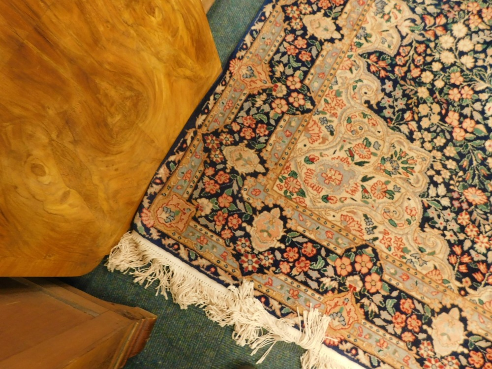 A Persian rug, with a design, decorated with flowers in navy, surrounded by cream and pale blue span - Image 2 of 3