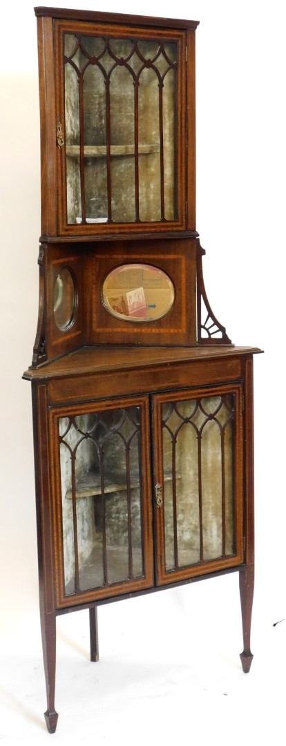 An Edwardian mahogany and satinwood crossbanded standing corner cabinet, the top with a glazed door
