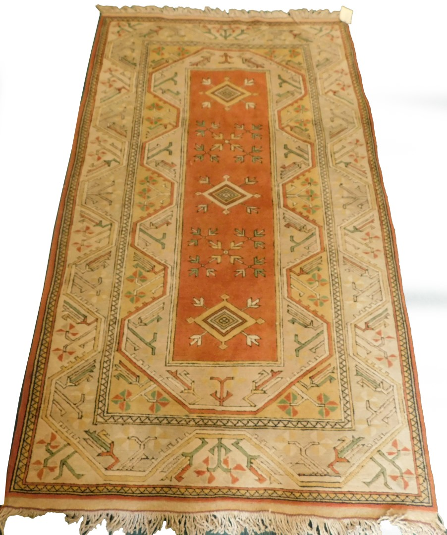 A Turkish rug, with a multi coloured geometric design, on a cream ground with multiple borders, 216c