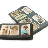 An album containing a number of late 19th/early 20thC greetings cards, various subject matters, etc.