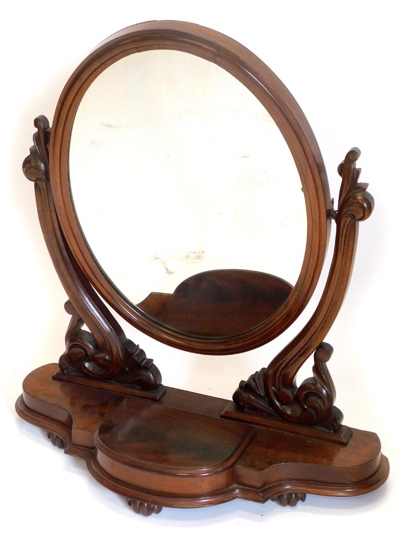 A Victorian mahogany dressing table mirror, the over plate on pierced carved supports, with shaped b