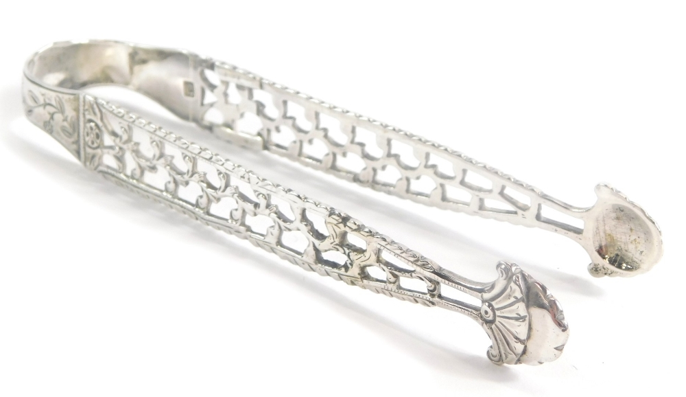 A pair of Georgian silver sugar tongs, with pierced decoration and engraved with a monogram, flowers