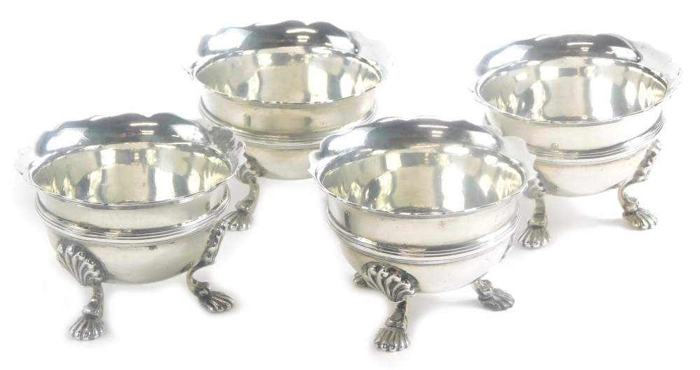 A set of four George V silver salts, by Wakely and Wheeler, with a shaped rim and decorative banding