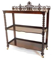 A Victorian rosewood three tier whatnot, with fret carved back, three shaped shelves, each on spiral