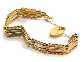 A 9ct gold gate bracelet, with four bar design and waved detail for the bottom links, with padlock a
