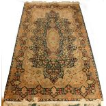 A Persian rug, with a design, decorated with flowers in navy, surrounded by cream and pale blue span