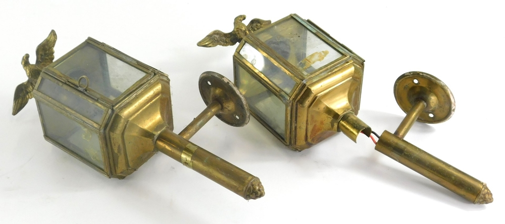 A pair of early 20thC brass coaching lamps, each with eagle finials, glass centres and turned circul