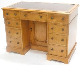 A 19thC birdseye maple pedestal desk, the top with a brown leather border, above an arrangement of n