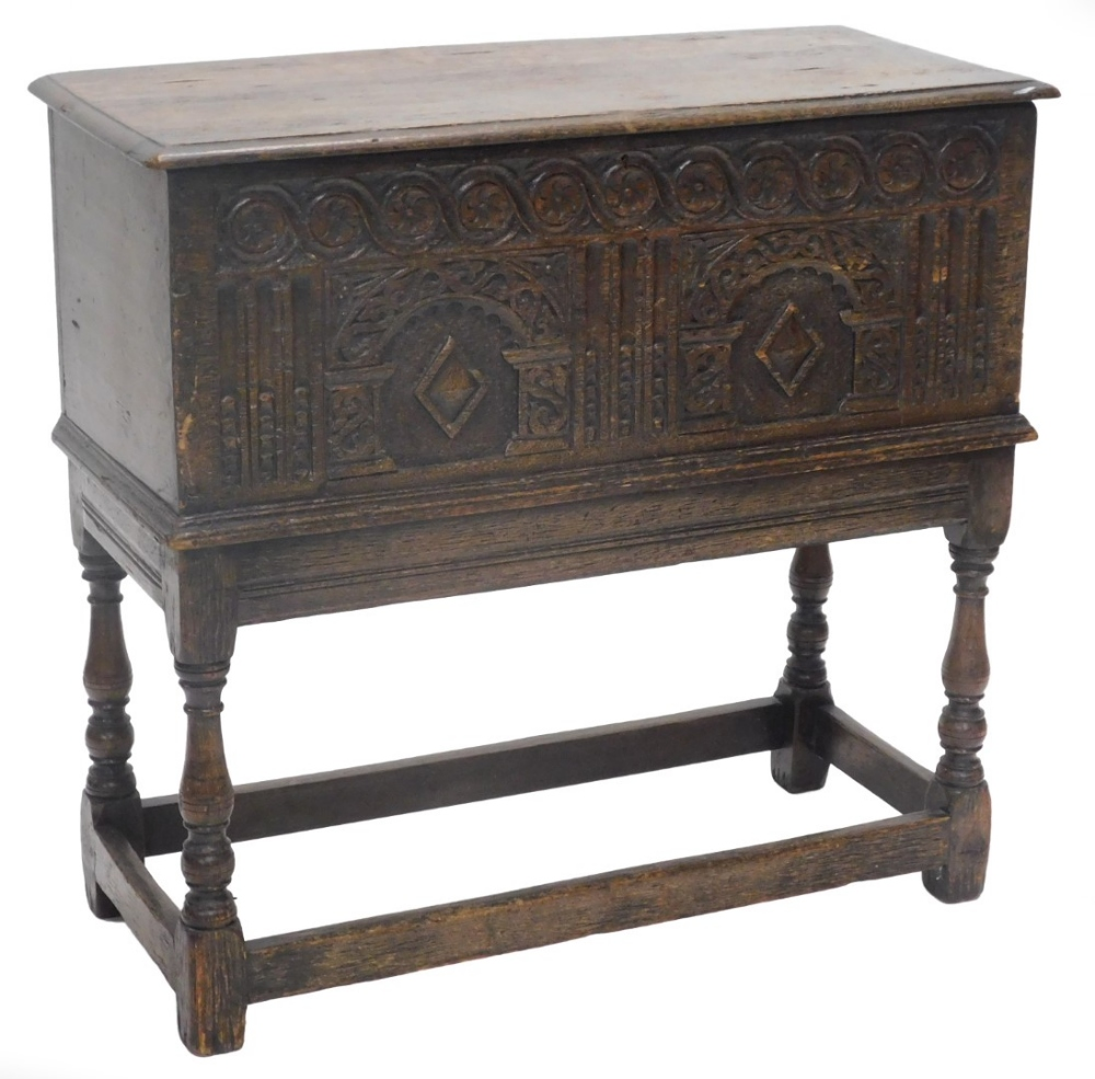 An oak chest, the rectangular top with a moulded edge above an elaborately carved frieze of arches,