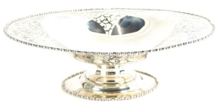 A George V silver dish, of shaped oval form, with part pierced body, on a squat stem and oval foot,