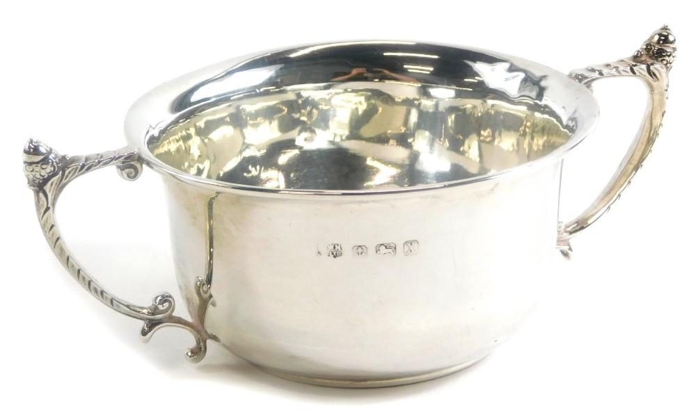 A George V silver two handled cup, of plain form with angular scroll handles each cast with an acorn