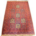A Balouch type rug, with a design of medallions, in navy and cream on a red ground with multiple bo