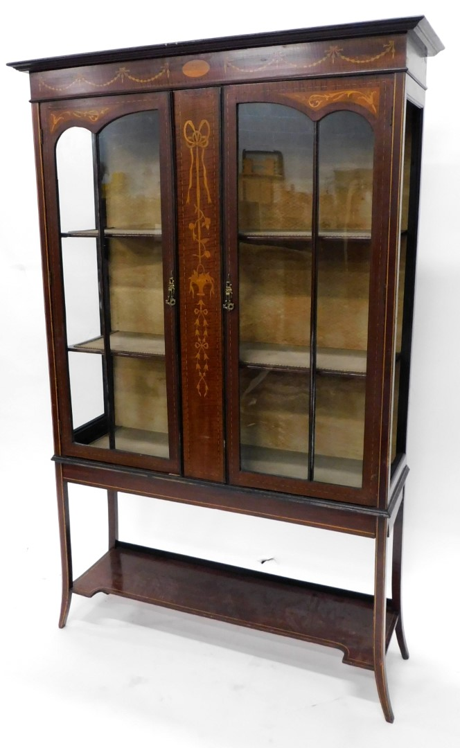 An Edwardian mahogany marquetry display cabinet, the top with a moulded cornice with two astragal gl