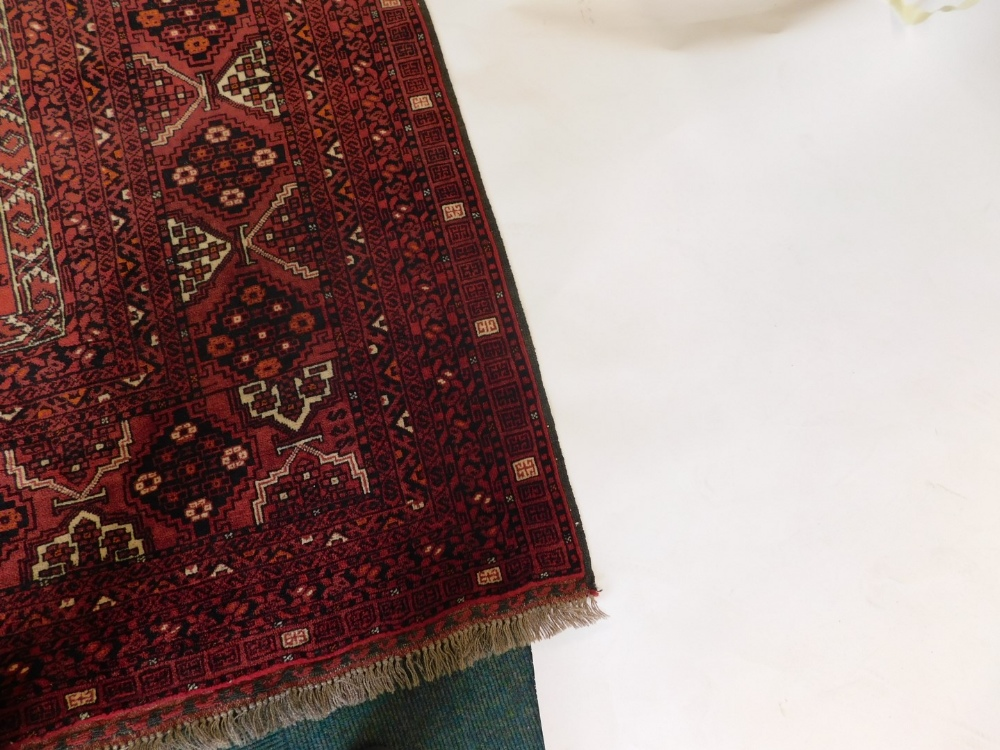 A Balouch type rug, with a design of medallions, on a red ground with multiple borders, 243cm x 171c - Image 2 of 3