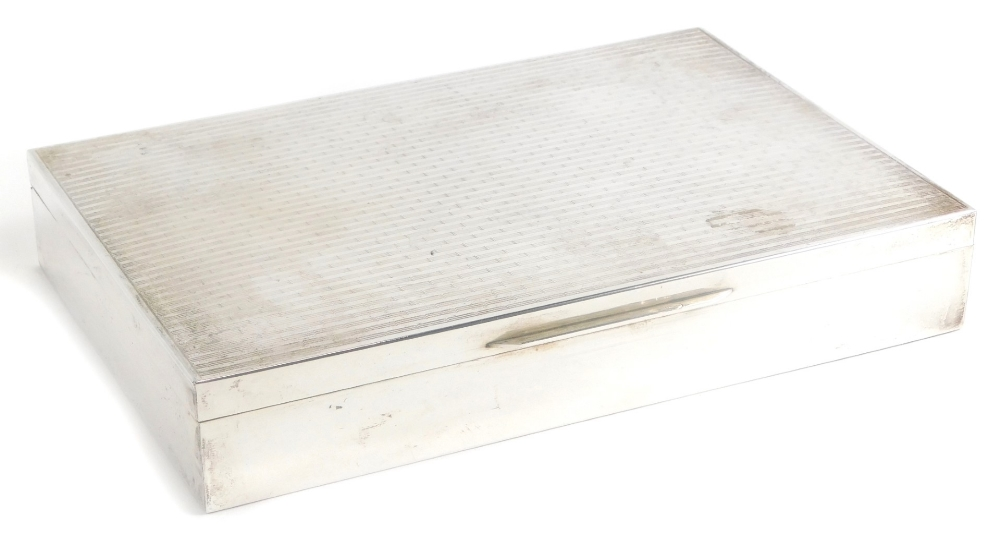 An early 20thC white metal cigarette box, of rectangular form with engine turned decoration, the hin