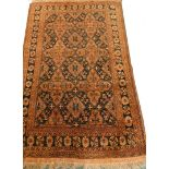 A Balouch type rug, with a design of medallions, in rust coloured medallions on a navy ground with m