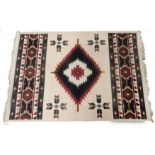 A modern rug, with a geometric design on a cream ground, 119cm x 165cm.