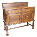 A 1920s oak sideboard, with a raised back above two short drawers and two panel doors, on spirally t