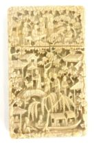 A 19thC Chinese carved ivory card case, decorated with figures, buildings, bridge, flowers, etc., 11
