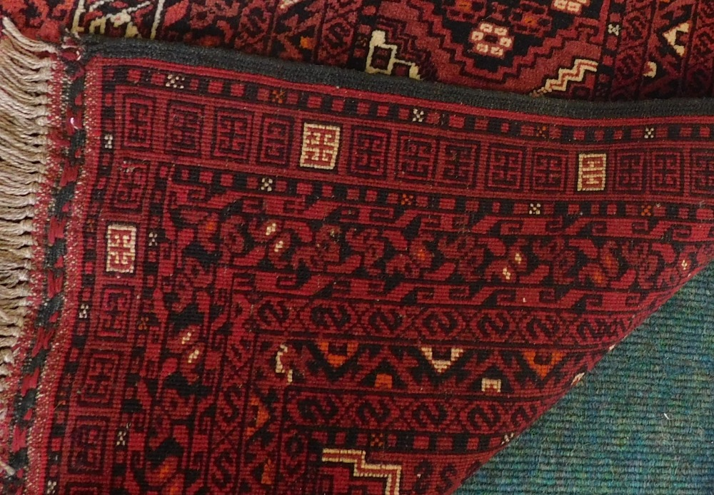 A Balouch type rug, with a design of medallions, on a red ground with multiple borders, 243cm x 171c - Image 3 of 3