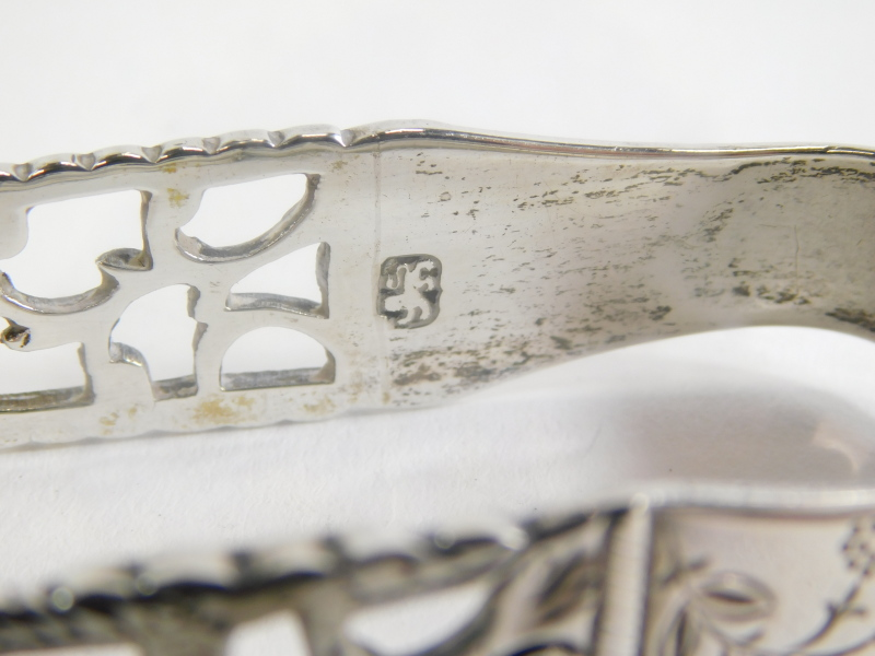 A pair of Georgian silver sugar tongs, with pierced decoration and engraved with a monogram, flowers - Image 2 of 2