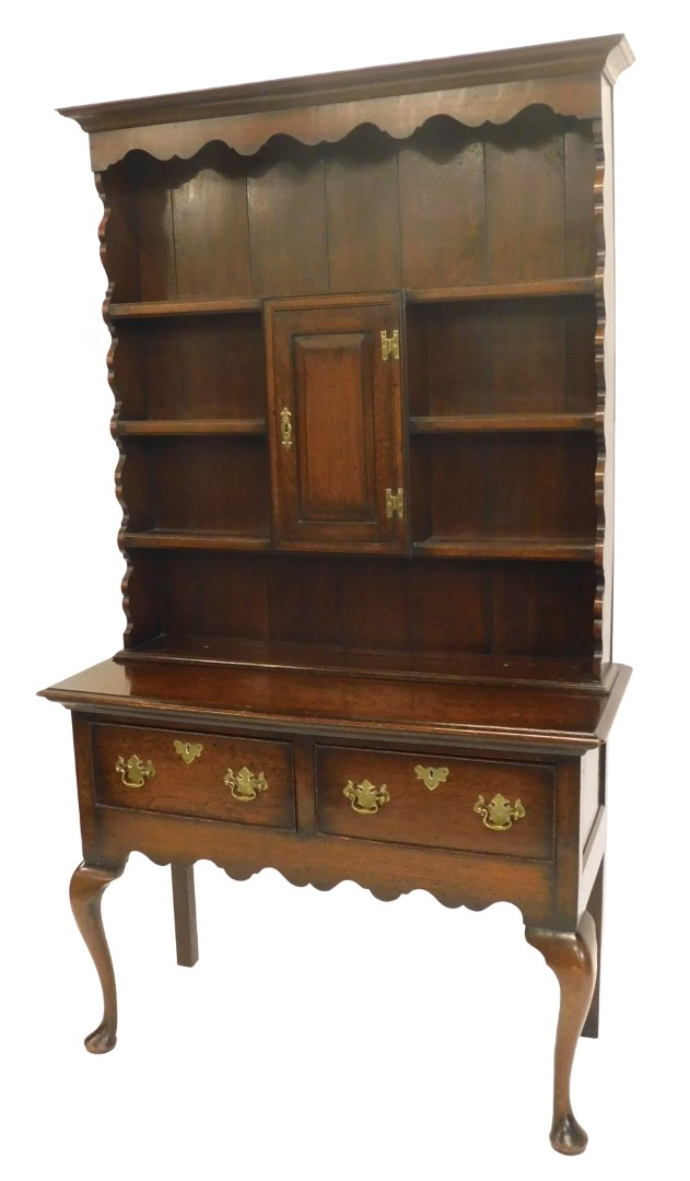 An oak dresser in 18thC style, the top with a raised border above three plate shelves, the base with