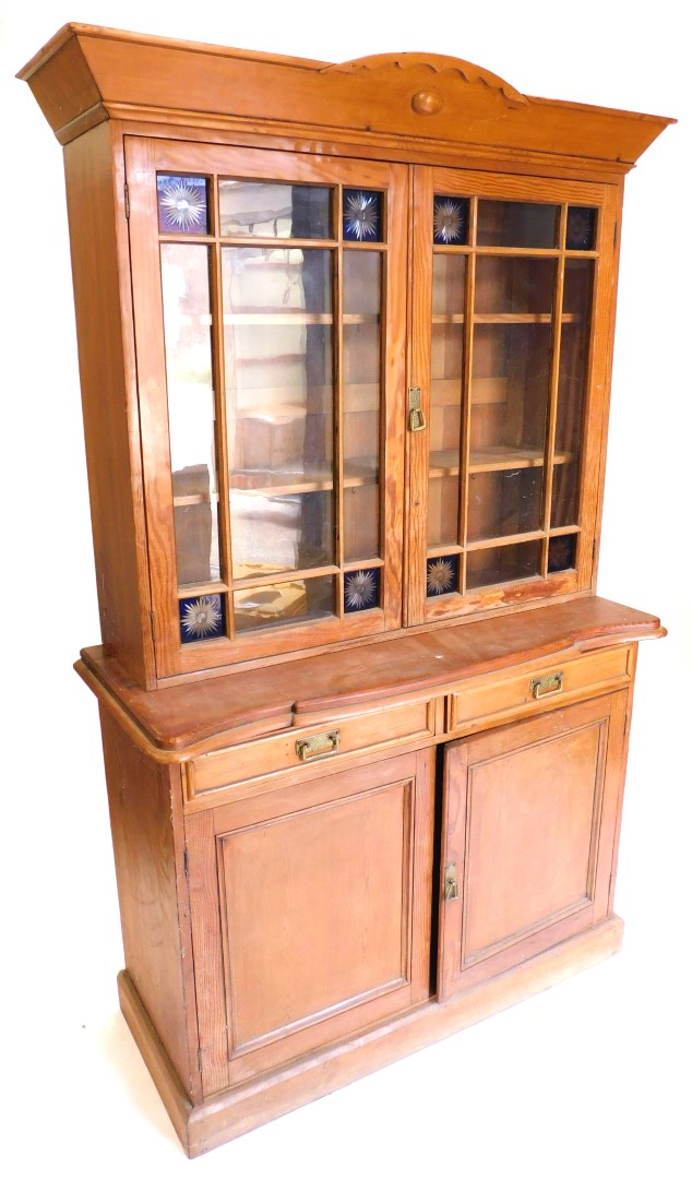 A pine and pitch pine cabinet, the top with a shaped cornice above two glazed doors inset with engra