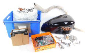 A Harley Davidson fuel tank, handle bar and assorted Harley Davidson spares.
