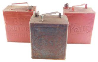 Three petrol cans, comprising Esso, BP and Pratt's.
