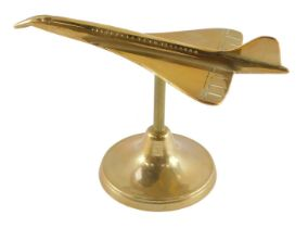 An aeronautical brass desk stand, modelled as Concorde 18.58, 18.5cm wide.