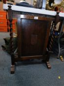 An oak fire screen, with barley twist columns and central floral panel.
