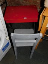 A child's wooden desk, painted red and black, together with a chair painted grey. (2)