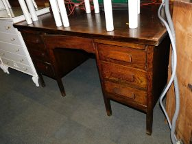 A mid 20thC oak veneered desk, with five drawers raised on block feet.