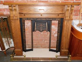 An oak fire surround, with cast iron inset, lacking tiles, with marble base, and brass fender. (4)
