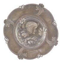An Art Nouveau late 19thC pewter circular dish, pierced and embossed with a bust portrait of a lady,