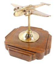 A brass desk stand modelled as a World War II bomber plane, raised on a shaped oak base, 19cm wide.