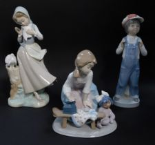 Three Lladro porcelain figures, comprising a kneeling girl with doll and ironing board, standing gir