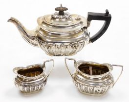 A Victorian silver three piece tea service, with ebonised handle and fluted body comprising teapot,