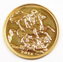 An Elizabeth II full gold sovereign, dated 2014, in plastic coin casing.