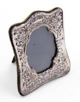 A silver photograph frame, with floral scroll embossed decoration and blank cartouche, oval aperture