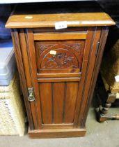 An oak pot cupboard, with carved panel door.