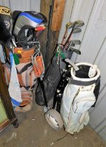 Various golf clubs and caddy bags, together with a shooting stick.