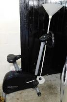 A Reebok exercise bike, and a white standard lamp. (2)