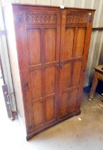 An oak hall robe, with carved design top and drop handles, on bracket feet.