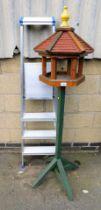An aluminium step ladder and a bird table.