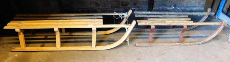 Two wooden sleds, comprising a Davos wooden sled and another with metal runners. (2)