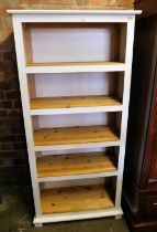 A white painted modern pine bookshelf, with five shelves.